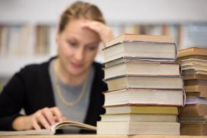 Lernende Frau mit Bücherstapel