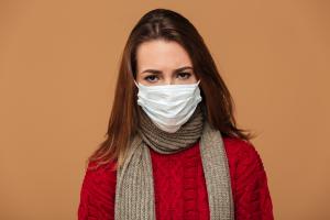 Frau mit Pullover, Schal und Mundschutz