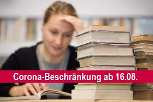 Lernende Frau mit Bücherstapel; Schriftzug: Corona-Beschränkung ab 16.08.
