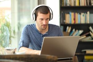 Mann mit Headset sitzt vor einem Laptop